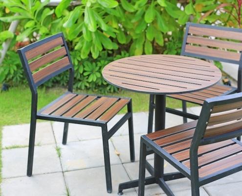 3 chaises et une table ronde en métal et bois dans un jardin